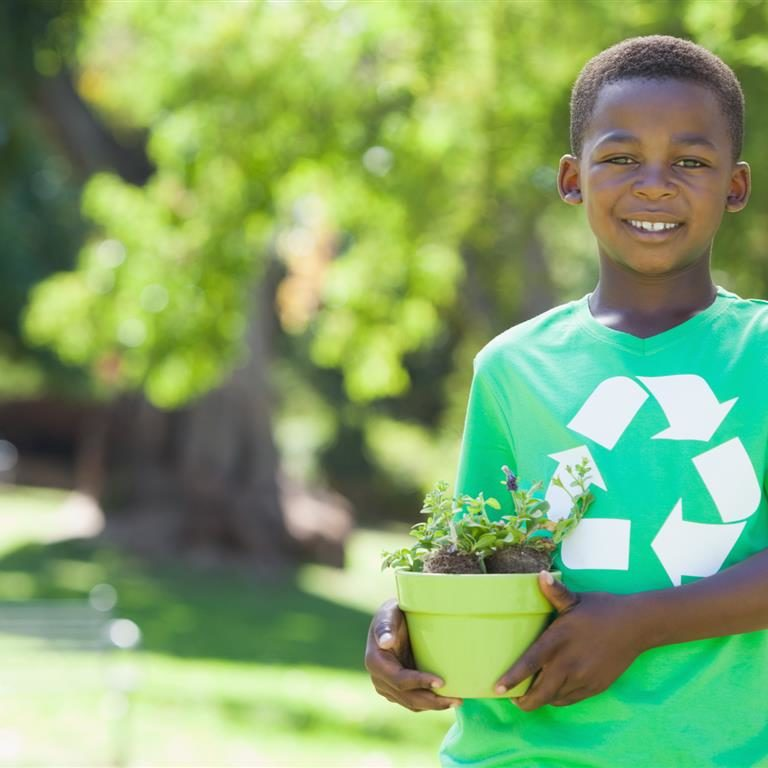 Young boy in recycling tshirt holding potted plant on a sunny day