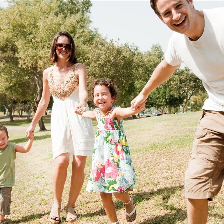 Young family playing and running with two young children, focus on the father